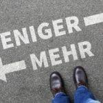 """Straße mit Kreidezeichnung """"Weniger"""" ist """"Mehr"""""""